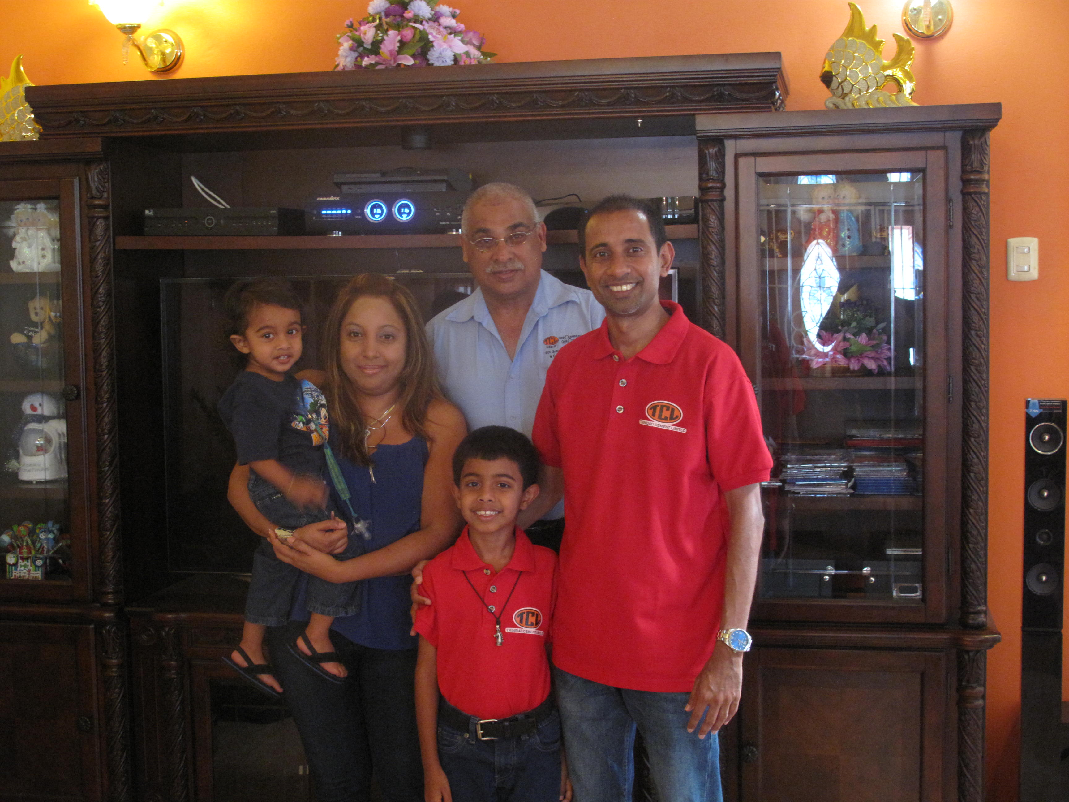 TCL's General Manager (Ag.), Jinda Maharaj with Rayden Rampersad's family at their home in Claxton Bay